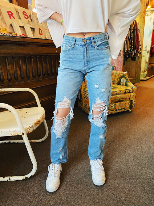 Distressed Mom Jeans at Multitudes Boutique - The Tawny Mom Jean is perfect for spring! These Lightwashed Mom Jeans have a straighter fit and hit at the ankle. These High Rise Mom Jeans have exaggerated distressing on the knees. Destroyed Mom Jean! Multitudes Boutique. Cutest Online Clothing Store.