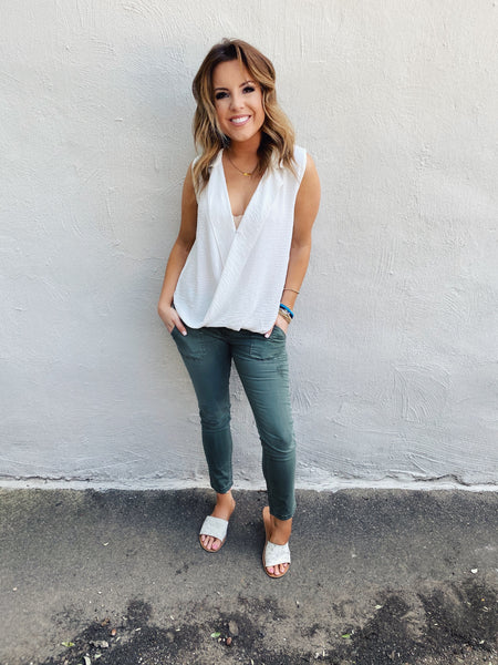 Surplice Tops are fun to wear, and this White Sleeveless Surplice Top can be worn year-around! This wrap top has a collar, a snap to keep it from opening, is longer in the back, and has that wrap surplice detail in the front. Wear alone or layer! Multitudes Boutique. Cutest Online Boutique. Free Shipping over $65.