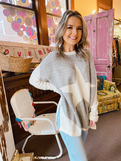 Star Tops at Multitudes Boutique - The Star Bright Sweater is a fun addition to any closet! This Star Sweater is soft and cozy. This Oversized Knit Sweater is white, except for the grey front. The best part of this Star Top is the bright white star right on the front! Multitudes Boutique. Cutest Online Clothing Store.