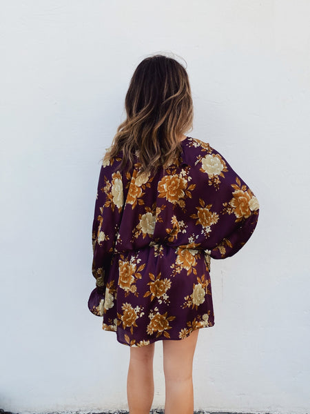 Look stunning in this Long Sleeve Wrap Dress! This Dolman Sleeve Floral Wrap Dress will go from Day to Night in a flash! You need this Dolman Sleeve Dress in your life! The gold floral print on a burgundy background is gorgeous! Long Sleeve Wrap Dress by Multitudes. Multitudes Boutique. Cutest Online Boutique.