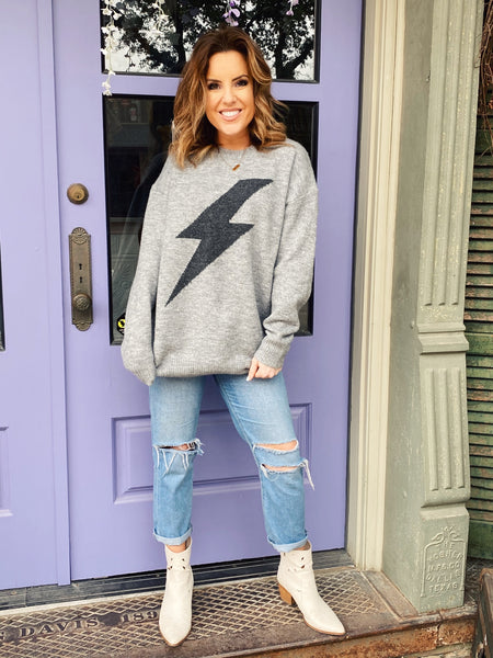 Lightning Bolt Sweater by Multitudes - The Grey Lightning Bolt Sweater is soft, cozy, and trendy. We love the tone-on-tone of the heather grey marled background and the charcoal gray thunder bolt. Wear this lightning bolt sweater with your leggings all fall and winter! Multitudes Boutique. Cutest Online Boutique.