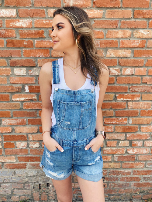 Slow it down a bit while wearing The Betty Denim Shortalls! These Overall Shorts for Women are perfect for those Saturday strolls on warm summer days! These Shortalls feature adjustable straps, a wide front pockets, side metal buttons, cuffed hems, and distressing. Multitudes Boutique. Cutest Online Clothing Store.