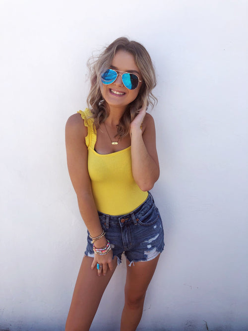 Are Ruffle Strap Bodysuits on your wishlist? Then grab this Yellow Ruffle Strap Bodysuit! This Ribbed Ruffle Strap Bodysuit is bright and cheery, just like you! So, pair your favorite High Waisted Distressed Mom Shorts with this cute ruffle bodysuit for an easy go-anywhere look all summer long! Multitudes Boutique.