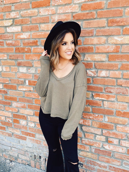 Long Sleeve Crop Tops are trending and you will love this Olive Thermal Crop Top. This fall crop top is made of waffle knit in olive! The edges of this waffle crop top are raw and frayed. This long sleeve crop top has dolman sleeves and can be worn off shoulder.  Multitudes Boutique. Cutest Online Boutique.