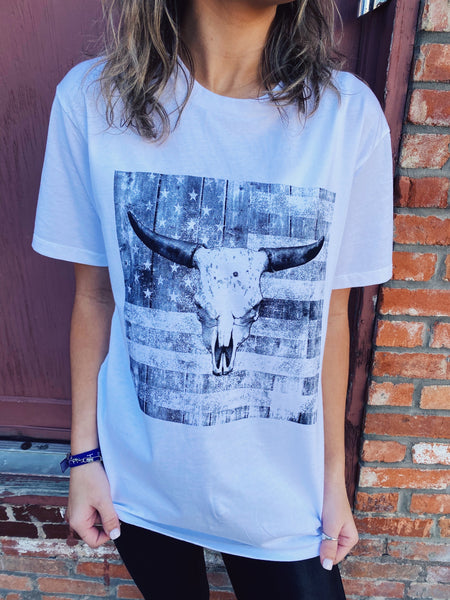 Women's Graphic Tees at Multitudes Boutique - The American Bull Graphic Tee is printed on a 100% Cotton White Tee so it's soft and will get better with age! This vintage graphic tee features a distressed American Flag with a distressed bull skull layered on top. Multitudes Boutique. Cutest Online Clohing Store.