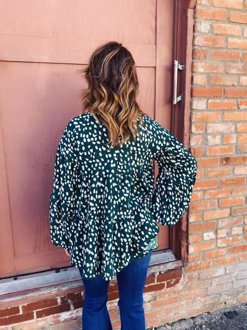 Tiered Dalmatian Top at Multitudes Boutique - This Tiered Hunter Dalmatian Print Top is trendy! This Babydoll top is hunter green dalmatian print, is long sleeved, has an oversized fit, is longer like a tunic, and has three tiers. Wear it for holiday and all season long. Multitudes Boutique. Cutest Online Boutique.