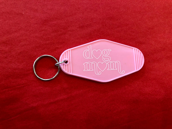"Dog Mom Motel Keychain Vintage style motel keychain is a shoutout to all the dog mamas out there! Keychain is 3.5"" pink plastic with a 1.25"" keyring for all your keychains. Pink Motel Keychain says Dog Mom in white Made in United States of America. Stocking Stuffer. Multitudes Boutique. Cutest Online Boutique."
