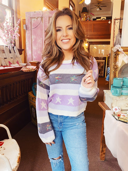 Star Sweater at Multituedes Boutique - The Stars at Dusk Sweater is adorable! This Colorful Sweater has lilac stripes, some of which have white stars. This Lavender Sweater also has a contrast of rainbow colored stars! This Multicolor Sweater is special! Multitudes Boutique. Cutest Online Clothing Store.