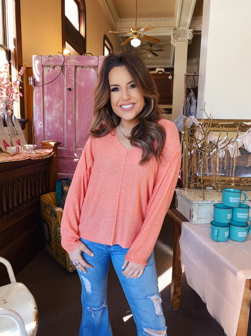 Lightweight Sweaters at Multitudes Boutique - The Peach Oversized V-Neck Sweater is the perfect lightweight sweater. This Oversized Sweater can be worn off the shoulder. This Off the Shoulder Sweater is peach, and has reversed seams detailing. Multitudes Boutique. Cutest Online Clothing Store.