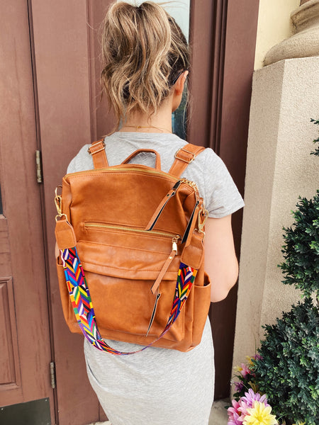 "Grab the Brielle Convertible Backpack in Camel to carry all the things you can't live without...and look trendy while doing so! You will love the detachable, colorful guitar style strap and all the compartments of this Convertible Bag! Vegan Leather. 13.5 x 12.5"" x 5"". Multitudes Boutique. Cutest Online Clothing Store."