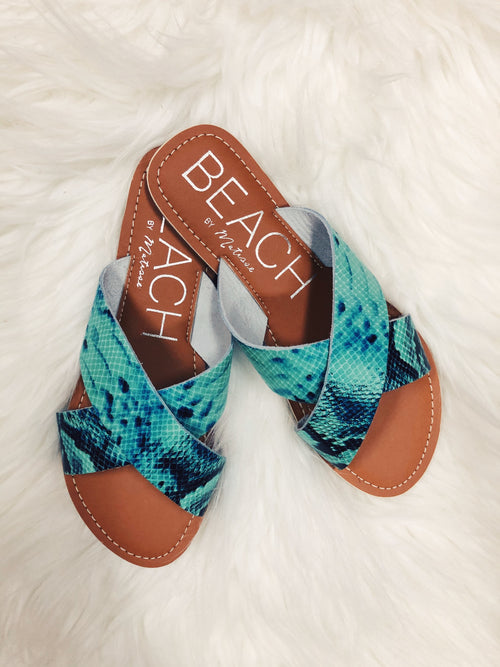 The Pebble Blue Snake Sandals by Matisse Coconuts, are a great new classic to add to your spring and summer wardrobe! Snakeskin is still trending, and we love this turquoise and black mix. It will go with so much and add that special pop of color!! We also love the criss-cross style. They are so easy to slide in and out of and are also super comfy with their padded footbed! Trust us, you will wear these on repeat all season long! The Pebble is an essential slide sandal with two criss-cross straps