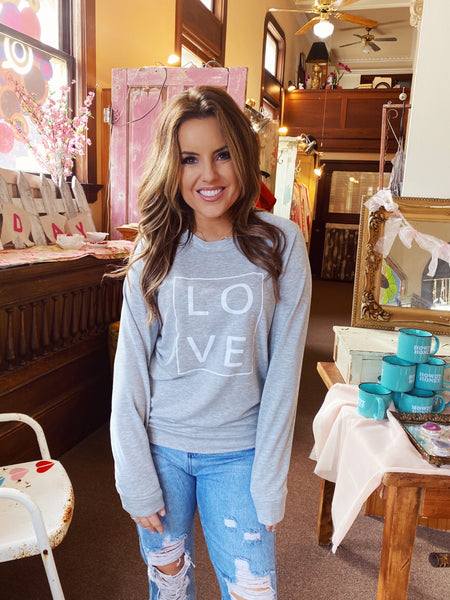 Love Sweatshirts at Multitudes Boutique - The Love in a Box Sweatshirt is a classic! This Valentine's Day Shirt can be worn all year long. This Love Sweatshirt is printed on a heather grey classic crewneck and is super soft and comfy! Heart Sweatshirt. Love T-Shirt. Multitudes Boutique. Cutest Online Clothing Store.