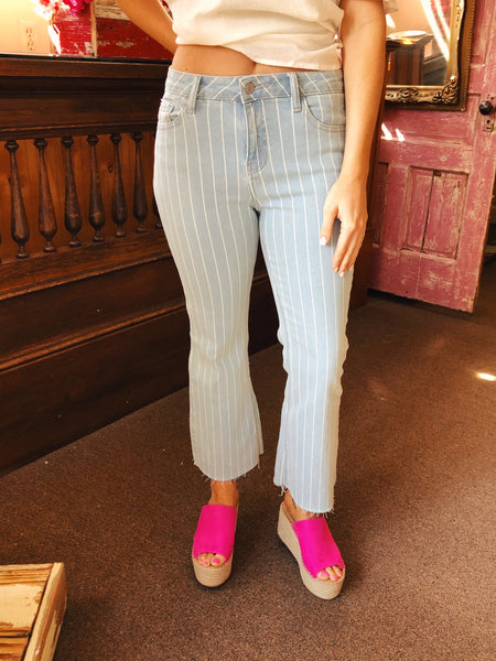 The Surely Striped Crop Flare Jeans are a must have this Spring! These light-denim jeans present a mid-rise waist, button and zipper detail, and front/back hand-pockets. White vertical stripes paired with the distressed and cropped flared hemline! Big City Trends, Small Town Prices. Light-Denim. Flare. Crop. Stripes. Surely Striped Crop Flare Jeans - Trendy Flare Jeans - Multitudes