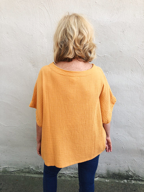 Looking for cute Fall Transitional Tops? Check out this Marigold Gauze Poncho Top! Gauze Poncho Tops are great as they can we worn all year long. Especially when they are the color of this Marigold Gauze Poncho Top! Front tuck into your favorite jeans and add your booties. Multitudes Boutique. Cutest Online Boutique.