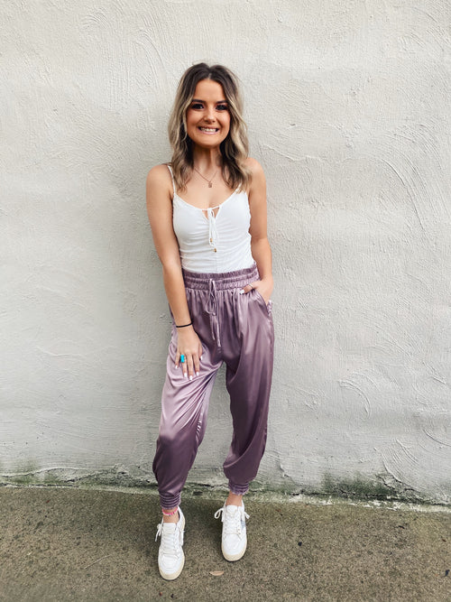 Satin Joggers are trending, and this pair of Misty Mauve Satin Joggers are the prettiest ones we've seen! We love the sporty, but feminine vibe! Trust us, you will LOVE how these satin joggers fit and feel! Wear with sneakers for a cute street style look! Multitudes Boutique. Cutest Online Boutique. Free Shipping $75.