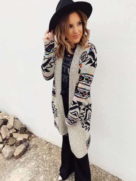 Aztec Cardigans are trending. This Multicolor Aztec Cardigan will be your go-to Aztec Cardigan all season long! Throw it on with your flares, a Honeysuckle Tee, and flat brim for a fun fall look! Aztec Cardigan by Multitudes. Honeysuckle Tees. Multitudes Boutique. Cutest Online Boutique.