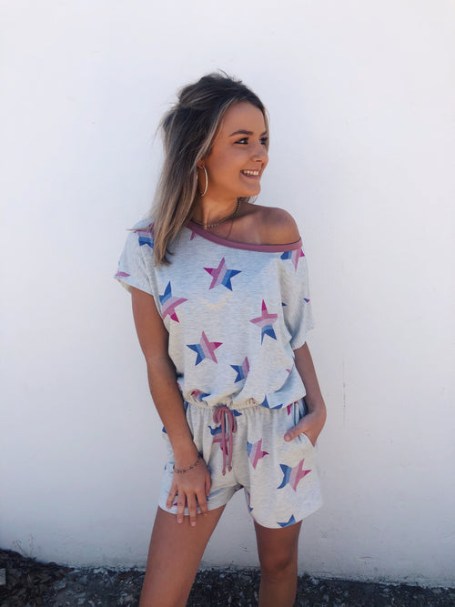 Are you into loungewear right now? We are, and we love the Rainbow Star Print Lounge Romper! It's so comfortable it could pass as a pajama romper! We love the star printed Heather Gray knit, the pink to blue hued rainbow stripes, and that it can be worn off the shoulder! Multitudes Boutique. Cutest Online Boutique.