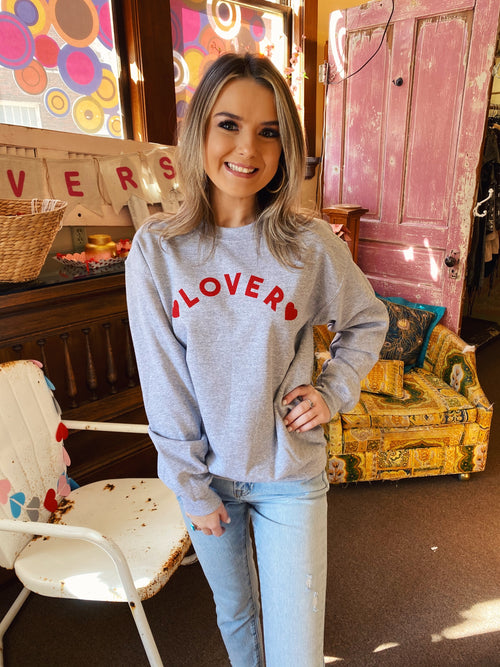 Love Sweatshirts at Multitudes Boutique - The Lover Sweatshirt is adorable! We love the positive vibe and the little red hearts make it perfect for Valentine's Day. This heart sweatshirt is heather grey and has red printing. This Valentine's Day Shirt is soft and cozy! Multitudes Boutique. Cutest Online Clothing Store