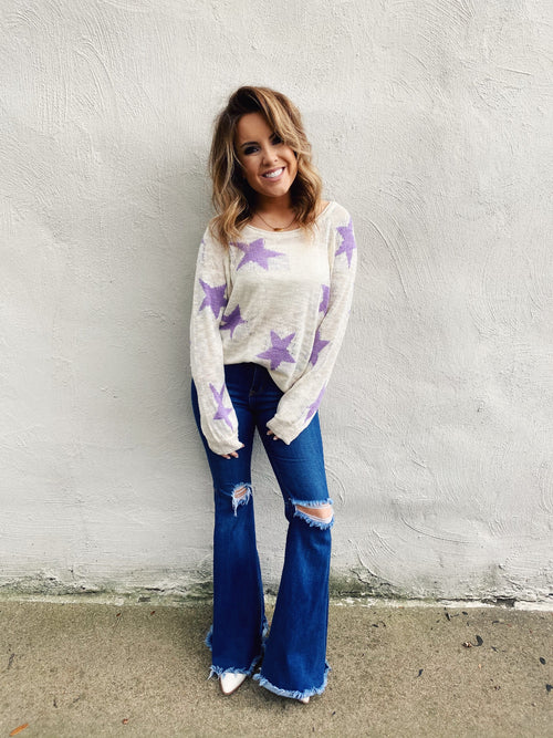 Looking for an Oversized Star Sweater? Check out the Lavender Lightweight Star Sweater! Pair it with your distressed mom jeans and sneakers for a cute everyday look, or pop it off one shoulder and pair with your distressed denim shorts, booties and hat for a punchy fun look! Multitudes Boutique. Cutest Online Boutique.