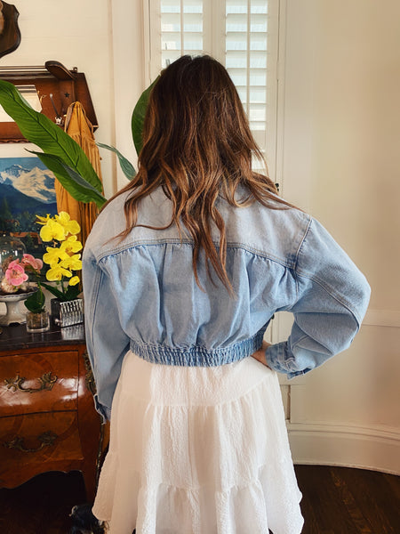 The Cora Cropped Denim Jacket is adorable and on-trend! This Light Wash Denim Jacket has an elastic waistband, a button closure, two front pockets with dart details, and a collar. You won't believe the fit and all the added details of this special Cropped Jean Jacket! Multitudes Boutique. Cutest Online Clothing Store.