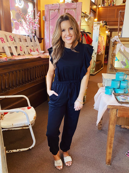 Black Sleeveless Jumpsuits at Multitudes Boutique - The Black Ruffle Knit Jumpsuit is adorable! The Ruffle Jumpsuit is made of soft black knit, has an elastic waist, jogger  ankles, and a ruffled flutter at the shoulders. This Jogger Jumpsuit is special! Multitudes Boutique. Cutest Online Clothing Store.