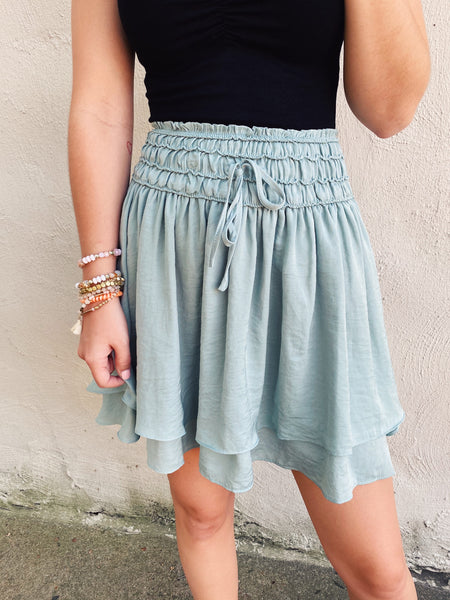 High Waisted Mini Skirts are trending and this Sage Layered Silk Mini Skirt is our favorite! We love that light color, shirred waist mini skirt, and tiered skirt! This is a great smocked miniskirt to add to your fall transitional outfits. Multitudes Boutique. Cutest Online Boutique.