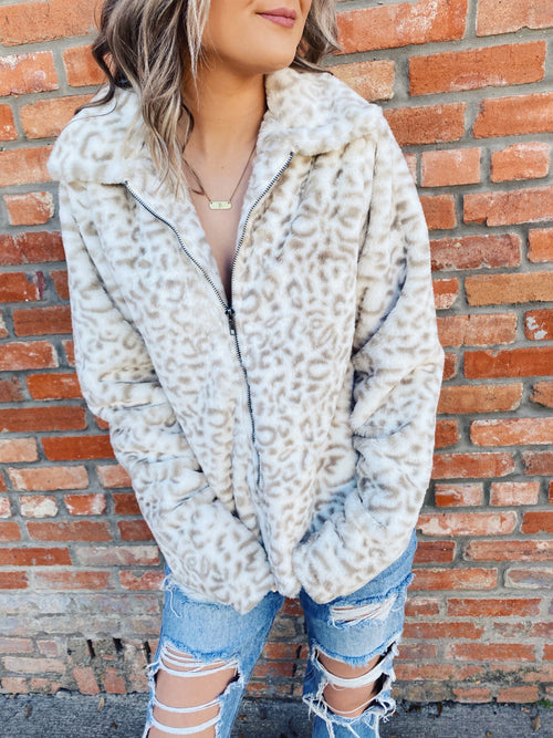 Leopard Fur Coat at Multitudes Boutique - The Fuzzy Leopard Zip Up Jacket has a tan leopard print on a cream faux fur background. This Leopard Jacket is fully lined, has a front zipper, a collar, and pockets. Leopard Fur Coat. Leopard Print Jacket. Multitudes Boutique. Cutest Online Boutique.