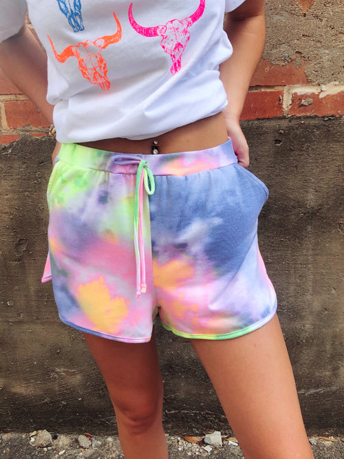 Hey summer-lovin girl, looking for a cute pair of bright tie dye shorts? Well, check out the Neon Tie Dye Lounge Shorts! You NEED these to wear over your bikini bottoms, to pair with a cute crop top or with your favorite Honeysuckle Tee! Multitudes Boutique. Cutest Online Boutique. Honeysuckle Tees.