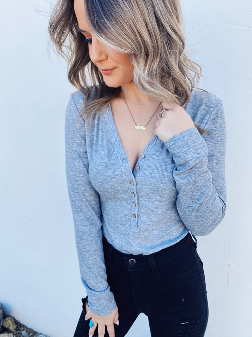 Long Sleeve Henley at Multitudes - The Grey Long Sleeve Henley Bodysuit is a MUST for your closet! This ribbed knit bodysuit has long sleeves, a v-neck, and seven wooden buttons down the bodice. The bodysuit has a two snap closure and a thong style. Long Sleeve Henley. Multitudes Boutique. Cutest Online Boutique.