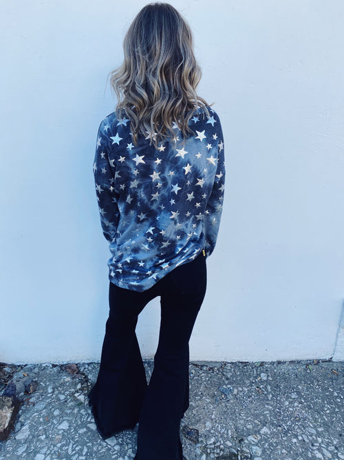 Cute Tie Dye Shirts at Multitudes Boutique - The Foil Star Tie Dye Top is so fun! The minute you walk in the party, everyone will want to know where you got this Star Sweatshirt! This charcoal tie dyed top has different sized silver metallic foil stars! Holiday Top. Multitudes Boutique. Cutest Online Boutique.