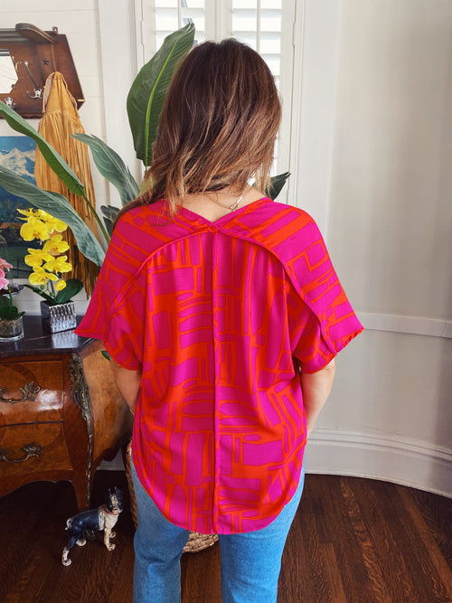 Dolman Sleeve Tops at Multitudes Boutique - The Magenta Anderson Top is a MUST! This V Neck Top is made of a modern bright magenta and orange print, fits oversized, has dolman sleeves, and a back seam. This Cute Summer Top offers coverage and comfort! Multitudes Boutique. Cutest Online Clothing Store.