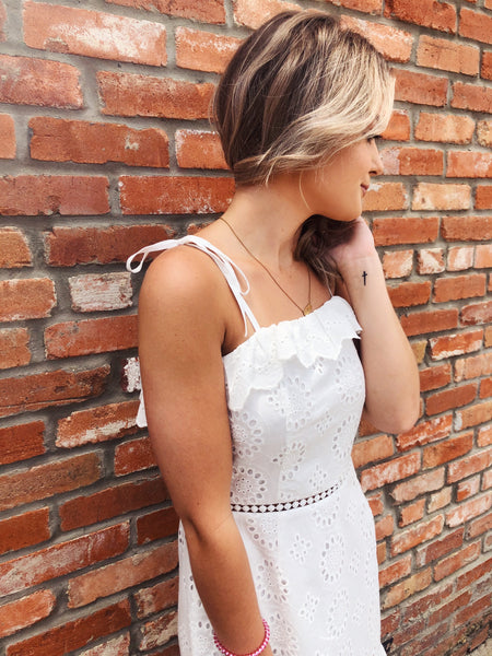 White Sundresses are a MUST for every summer wardrobe, and we love this White Eyelet Ruffle Dress! It's perfect for a White Graduation Dress if you're lucky enough to have a graduation this year, but this cute white summer dress would also be a great dress for any bride, or just any summer outing! Multitudes Boutique.