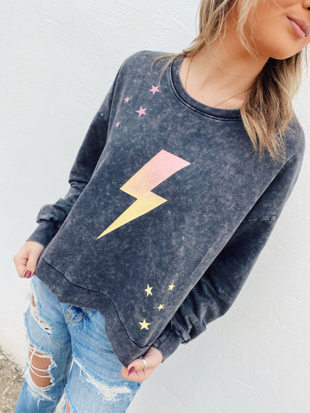 Acid Wash Sweatshirt by Multitudes - As far as Black Acid Wash Sweatshirts go, this Night Sky Acid Wash Sweatshirt is the cutest we've seen! This one is soft, has an ombre lightning bolt, pink stars, and yellow stars on the front. It's special! Multitudes Boutique. Cutest Online Boutique.