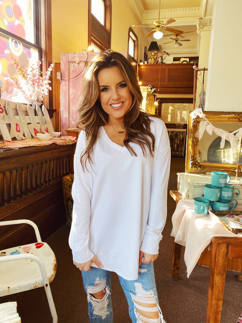 Women's White V-Neck T-Shirts at Multitudes Boutique - The V-Neck Weekender in White by ZSUPPLY is to die-for! This Oversized White T-Shirt is made of soft terry knit, has long sleeves, a curved hem in front, and a slightly oversized v-neck. Multitudes Boutiqe. Cutest Online Clothing Store.