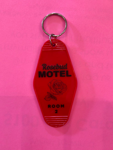 "Rosebud Motel Keychain. Vintage style motel keychain is a nod to the Motel that the Roses live in in Schitt's Creek. Keychain is 3.5"" red plastic with a 1.25"" keyring for all your keychains. Made in United States of America. Stocking Stuffer. Multitudes Boutique. Cutest Online Boutique."