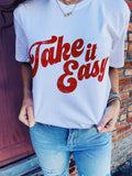 Women's Grahic Tees at Multitudes Boutique - The Take it Easy Graphic Tee is printed to look like a Vintage Rock and Roll Graphic Tee! This women's graphic tee is printed in red on a 100% Cotton White T Shirt. This Rock Tee is distressed. Multitudes Boutique. Cutest Online Clothing Store.