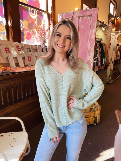 Lightweight Sweaters at Multitudes Boutique - The Pistachio Oversized V-Neck Sweater is the perfect lightweight sweater. This Oversized Sweater can be worn off the shoulder. This Off the Shoulder Sweater is sage green, and has reversed seam detailing. Multitudes Boutique. Cutest Online Clothing Store.