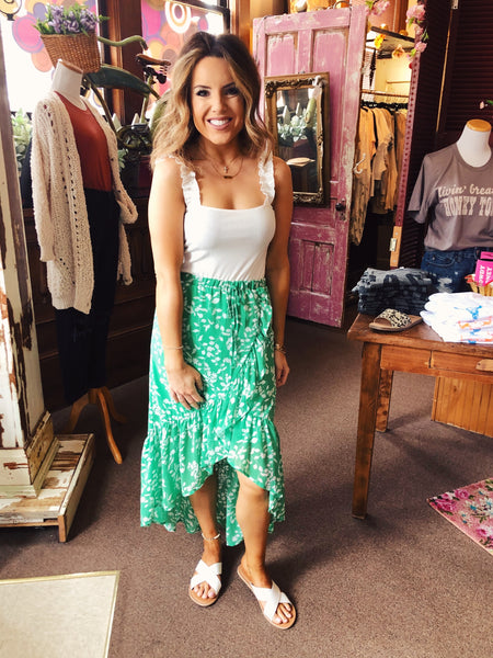 We love the feminine flair of the green Say So High Low Skirt! We love the pretty floral print in white on the green background, the elastic waist for ease and comfort, the simple self tie, and the high love hemline with the fun wide ruffle that gets bigger. Best Online Boutique. Multitudes Boutique. Free Shipping on Orders