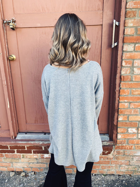 Waffle Knit Shirt at Multitudes Boutique - The Grey V-Neck Waffle Top is a great staple for your closet! The waffle knit is soft and cozy, the v-neck is oversized so you can wear it off one shoulder, and it's longer so it's perfect for leggings. Lounge Top. Multitudes Boutique. Cutest Online Boutique.