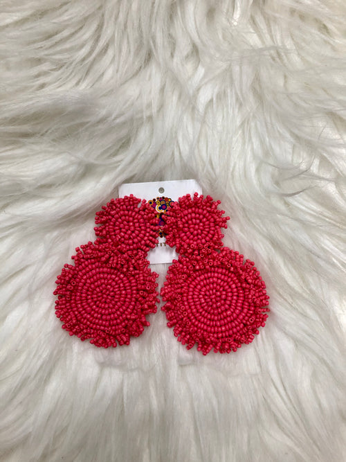 "We LOVE the Pink Cynthia Earrings! These dangling seed bead earrings are approximately 2"" long and are made of the prettiest coral-pink color. The beads are decorated in two circles with fringe, backed by felt. They will make all your summer outfits POP!"