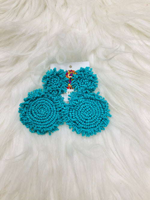 "We LOVE the Turquoise Cynthia Earrings! These dangling seed bead earrings are approximately 2"" long and are made of the prettiest turquoise color. The beads are decorated in two circles with fringe, backed by felt. They will make all your summer outfits POP!"