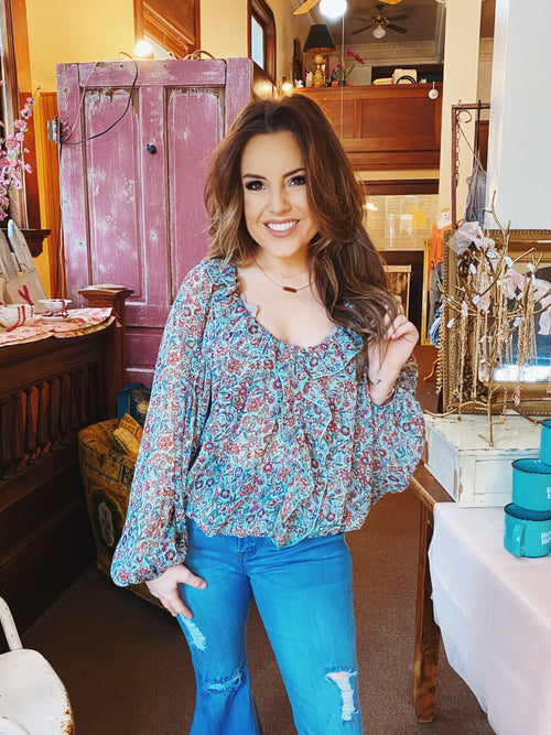 Ruffle Crop Tops at Multitudes Boutique - The Teal Floral Print Ruffle Crop is fun! This cute spring top is oversized, a bit boho, and has an elastic waitband that allows you to crop it as high as you want. This Ruffle Crop Top has a ruffle that goes around the neckline and down the front! Cutest Online Clothing Store.