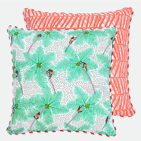 Create a tropical sanctuary with Safomasi's coral Coconut Pickers cushion. Inspired by Kerala's dreamy backwaters, this two-sided statement cushion with coconut pickers climbing palm trees on one side and a vibrant coral palm print design on the other will bring a sense of fun and colour to your home.