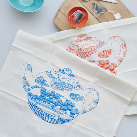 In the style of traditional blue Willow china is this stylish set of two tea towels in red and blue by Safomasi. Within the teapot itself and inspired by coastal scenes, each tea towel illustrates a picturesque view of racing yachts and homes overlooking the bay. Makes a lovely addition to a kitchen or a quirky gift for a loved one.