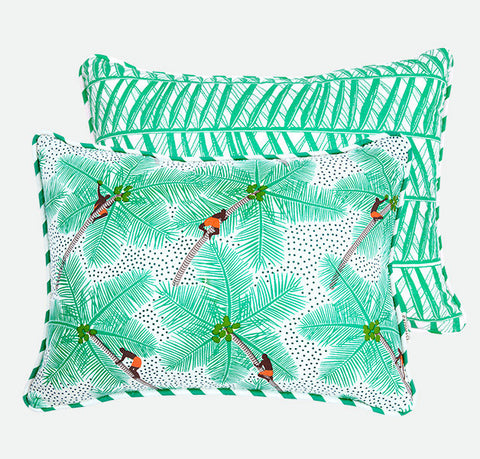 Create a tropical sanctuary with Safomasi's mint green Coconut Pickers cushion. Inspired by Kerala's dreamy backwaters, this two-sided statement cushion with coconut pickers climbing palm trees on one side and a vibrant mint palm print design on the other will bring a sense of fun and colour to your home.