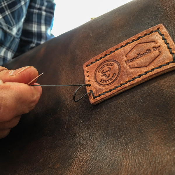 handstitching leather and wood bag
