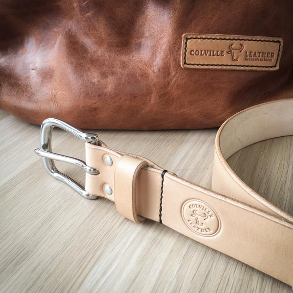 image of a Colville Leather handcrafter leather belt with Colville Leather's roll-top backpack in the background