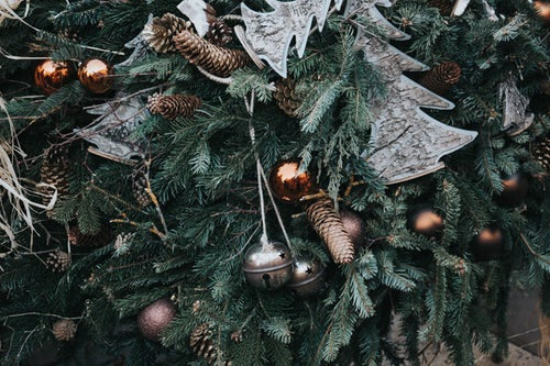 close up image of a Christmas tree decorated with bells, baubles and pine cones