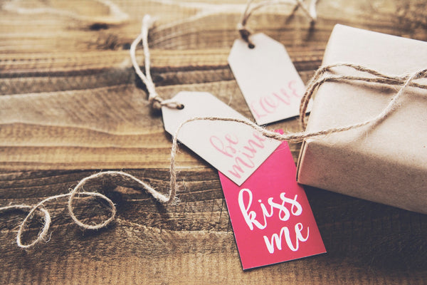 image showing a parcel with Valentines Day gift tags: 'kiss me', 'be mine' and 'love'