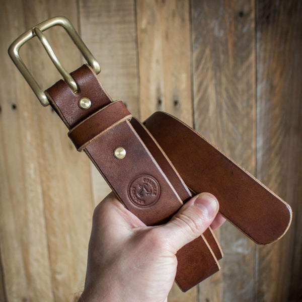 image showing man holding a rolled up Colville Leather handmade leather oak bark belt